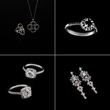 Luxury jewellery set. White gold or silver rings, earrings with crystals and pendant isolated on black. Selective focus. Royalty Free Stock Photography