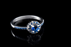 Luxury jewellery. White gold or silver engagement ring with colored gemstone closeup on black background. Selective focus. Stock Image