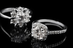 Luxury jewellery. White gold or silver engagement rings with diamonds closeup on black glass background. Selective focus. Stock Photo