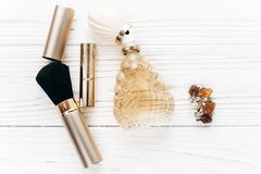Luxury jewelry perfume make up essentials flat lay on white rust. Ic wooden table in soft morning light. space for text. fashion blogger. modern woman stuff Stock Photography