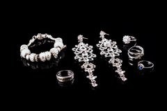 Luxury jewelry set. White gold or silver rings, earrings with crystals and pendant isolated on black. Selective focus. Royalty Free Stock Images