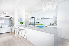 Luxury kitchen chairs and hanging lights with white walls Stock Image