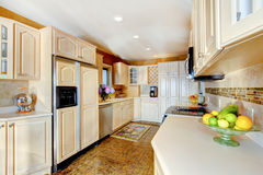 Luxury kitchen with cream cabinets, and white counter tops. Royalty Free Stock Images
