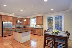 Luxury kitchen fitted with Viking appliances. Luxury kitchen with an island, light wood cabinets and Viking appliances stock photography