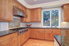 Luxury kitchen fitted with Viking appliances. Luxury kitchen with an island, light wood cabinets and Viking appliances stock photo
