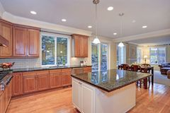 Luxury kitchen fitted with Viking appliances. Luxury kitchen with large island, light wood cabinets and Viking appliances stock image