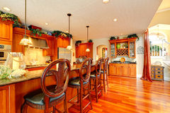 Luxury kitchen room with rich carved wood stools. Bright luxury kitchen with rich carved wood stools and granite counter top royalty free stock photos