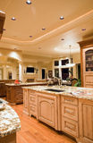 Luxury Kitchen with View of Living Room. Ornate kitchen and dining area in luxurious new home Royalty Free Stock Photos