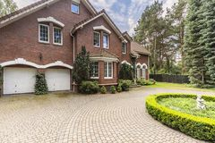 Luxury and large house in english style with garden and driveway. Concept royalty free stock photo