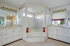 Luxury large white master bathroom cabinets with double sinks and big bath tub. Stock Images