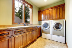 Luxury laundry room with wood cabinets. Stock Images