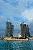 Luxury Lifestyle. Megayacht parked in front of highrise condos Stock Photo