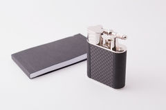 Luxury lighter. Black and silver vintage-style high-end lighter with notebook, interaction, brochure manual. Plain white background for e-commerce website Stock Photos