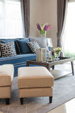 Luxury living room with blue classic sofa and pillows, wooden ta Stock Images