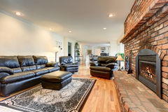 Luxury living room interior with black leather sofa set and brick fireplace. View of dining room Royalty Free Stock Photo
