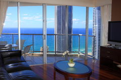 Luxury living room top floor with ocean view. Luxury living on a top floor in an apartment tower with a striking view to the pacific ocean from lounge with Stock Photography