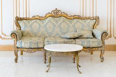 Luxury livingroom in light colors with golden furniture details. Elegant classic interior Royalty Free Stock Photos