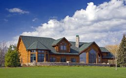 Luxury Log Cabin Home. A very modern log home ... country charm for the wealthy. Rural Wisconsin. Lots of blue sky Royalty Free Stock Image