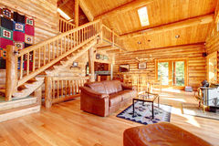 Luxury log cabin living room with leather sofa. Large luxury log cabin house living room with large staircase Royalty Free Stock Photography