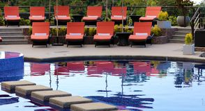 Luxury lounge chairs at Costa Rican premium travel hotel poolside. A landscaped high definition photo of resort hotel swimming pool with poolside chaise lounges Stock Photos