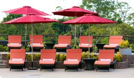 Luxury lounge chairs at Costa Rican premium travel hotel poolside. A landscaped high definition photo of resort hotel swimming pool with poolside chaise lounges Royalty Free Stock Images