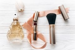 Luxury make up essentials brush and lipstick and perfume flat la. Y on white rustic wooden table with space for text in soft morning light. fashion blogger Stock Photo