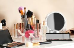Luxury makeup products and accessories on dressing table with mirror. Near wall royalty free stock photo