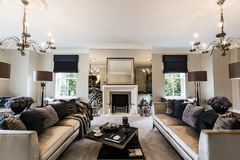 A Luxury Mansion Living Room With Feature Fireplace. Luxurious living room of a mansion with soft furnishings and a mirrored finish surround to the fireplace stock images