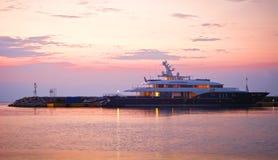 Luxury mega yacht. View of a luxury mega yacht in a marina at the dusk royalty free stock photo