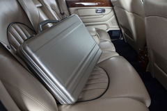 Luxury metal briefcase on the car back seat Stock Images