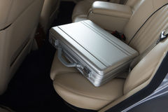 Luxury metal briefcase on a vinage car back seat. Stock Photography