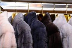 Luxury mink coats. Pink, grey, dark grey, pearl color fur coats on showcase of market. Stock Photo