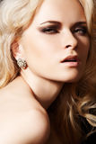 Luxury model with diamond earrings and blond hair. Fashionable close-up portrait of glamour woman model with sexy evening make-up & chic shiny jewellery Stock Photos