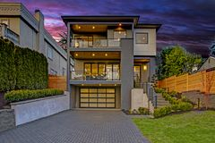 Luxury modern home exterior at sunset. Boasts four car garage with wide driveway stock photo