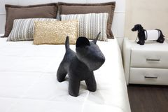Luxury modern style bedroom with toy black dog and different pillows on white bed, Interior of a hotel bedroom stock photos