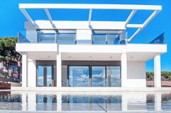 Free Luxury Modern White House With Large Windows Overlooking A Mediterian Landscaped Garden With Palm Trees And  Blue Swimming Pool. Stock Photography - 175282172