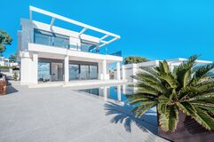 Free Luxury Modern White House With Large Windows Overlooking A Mediterian Landscaped Garden With Palm Trees And  Blue Swimming Pool. Stock Photo - 175282220