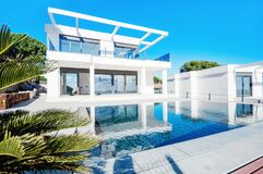 Free Luxury Modern White House With Large Windows Overlooking A Mediterian Landscaped Garden With Palm Trees And  Blue Swimming Pool. Stock Images - 175282424
