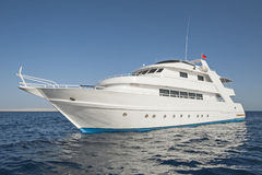 Luxury motor yacht at sea. Large luxury private motor yacht out on a tropical sea Royalty Free Stock Photos
