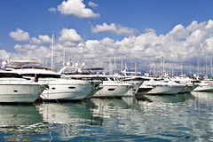 Luxury motor yachts. Row of luxury yachts mooring in a harbour on a sunny, cloudy, summer day Stock Image