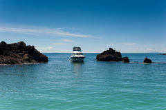 Luxury Motoryacht entering a cove Royalty Free Stock Image