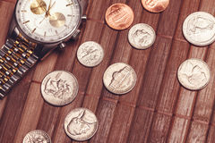 Luxury but not new watch with coins Royalty Free Stock Photos