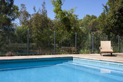 Luxury Outdoor Pool. A luxury outdoor pool with deck chair beside it Royalty Free Stock Images