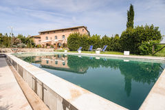 Luxury Outdoor Swimming Pool. Wide angle view of a luxury swimming pool in Tuscany (Italy Royalty Free Stock Images
