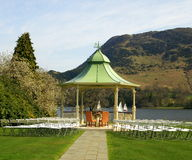 Luxury Outdoor Wedding Venue. Along the waterside of lake in gardens with seating and portico for ceremony Stock Image