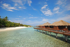 Luxury Overwater Villa connected to Beach. Luxury Overwater Villa connected to White Sandy Beach overlooking crystal clear water Royalty Free Stock Photography