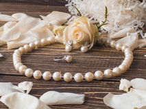 Luxury pearl necklace, ring and earrings with white rose petals, close up.  royalty free stock photos