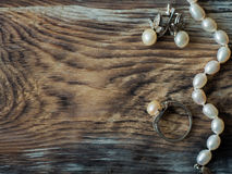 Luxury pearl necklace, ring and pearl earrings on old wooden table. with copy space, close up Stock Photos