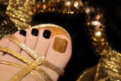 Luxury pedicure. Luxury pedicure with black and gold lacquer on women's toes on the black and brilliant background Stock Photography