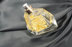 Luxury perfume with gold. Inside, on black silk background Royalty Free Stock Images